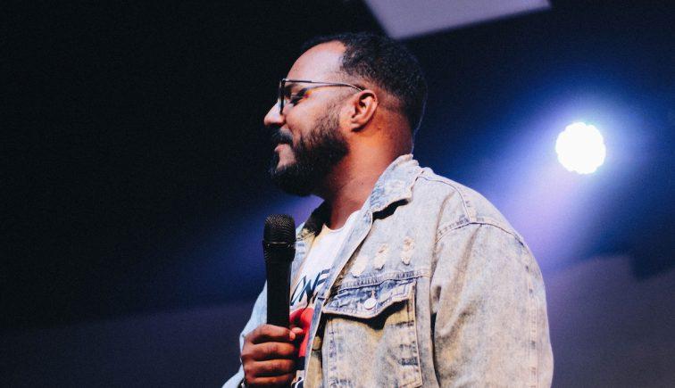 Black man preaching on stage